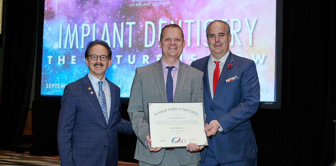 Dr. Walton is an Associate Fellow of the American Academy of Implant Dentistry. Photo shows Dr. Walton receiving his fellowship on a stage.